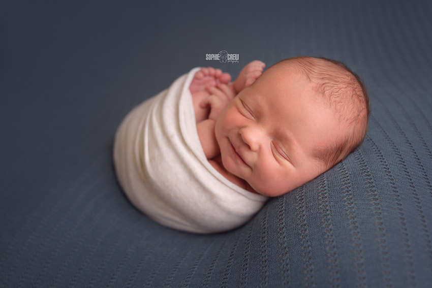 Smiling newborn swaddled in Sophie Crew's studio in San Diego
