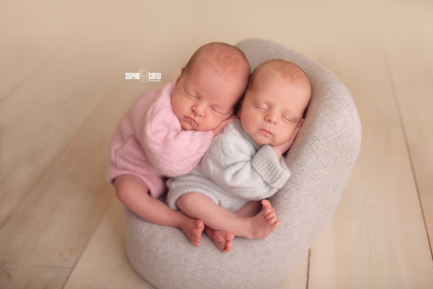 Newborn twins posed on posing chair