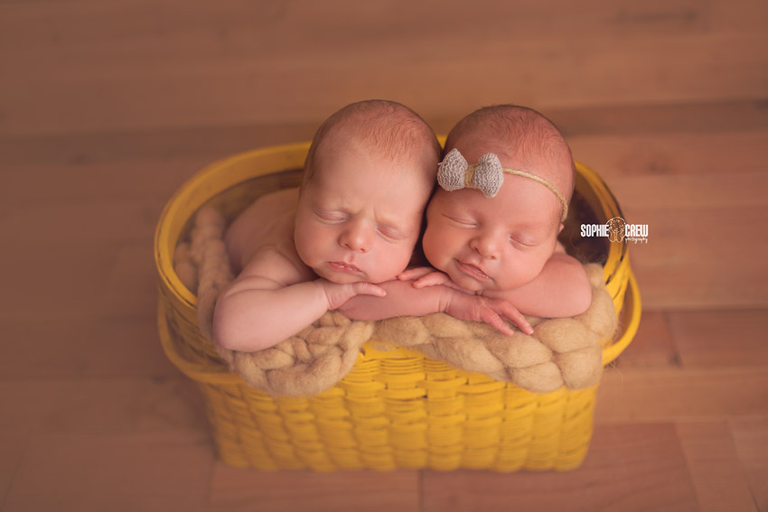 Newborn twin smile in basket prop