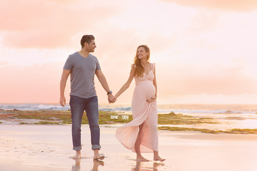 Expectant couple walks on beach during maternity photo session