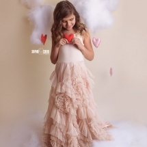 Girl in dollcake dress in bed of clouds holding a heart