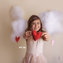 Girl holding red felt heart with puffy clouds in Dollcake dress