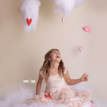 Photo session for Valentines Day with girl laughing as she catching falling hearts on a puffy cloud in the photo studio