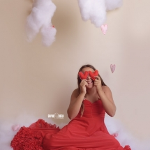 Girl wearing red fancy dress covers her eyes with red felt hearts sitting on a puffy cloud in the studio