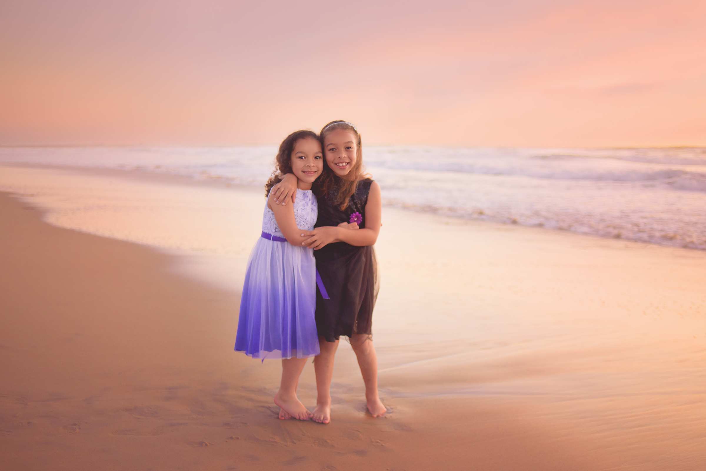 sisters pose at Mission Beach for their family photographer San Diego, CA