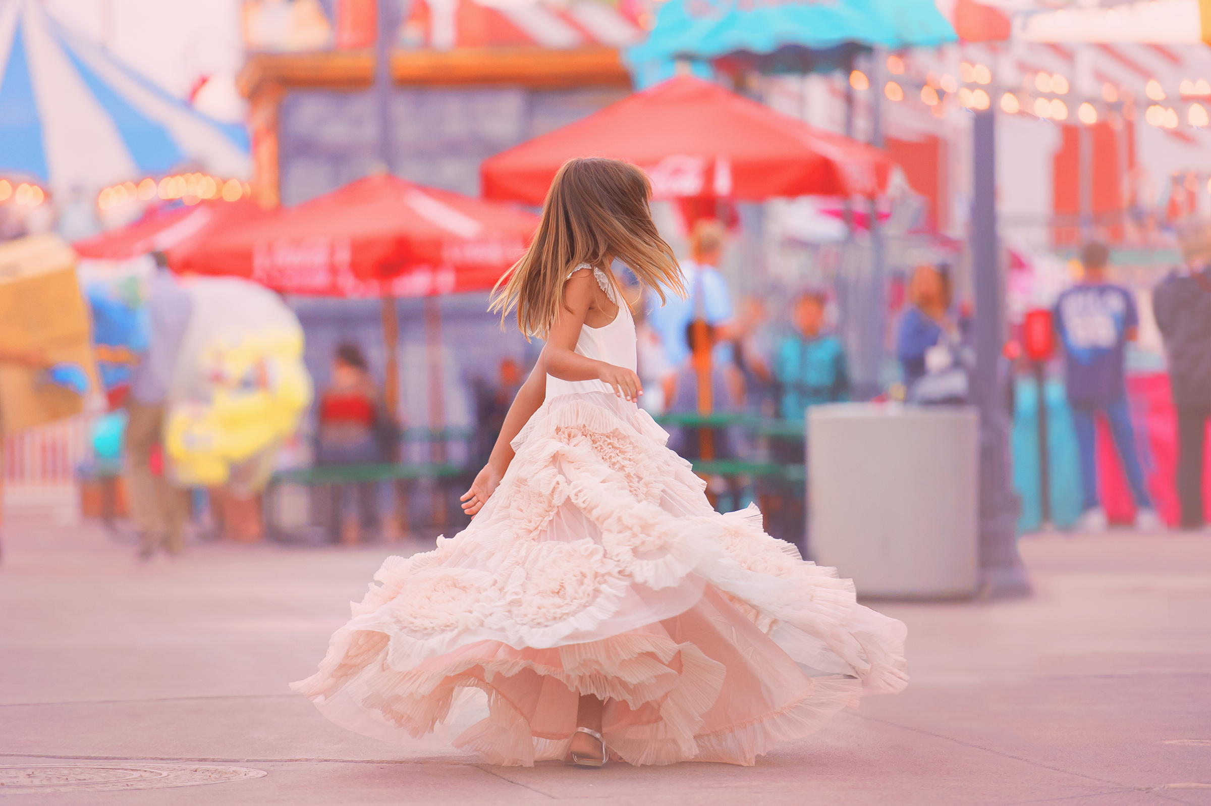 Family photo of girl in pink swirly dress at shoot at Belmont Park in Mission Beach with Sophie Crew Photography