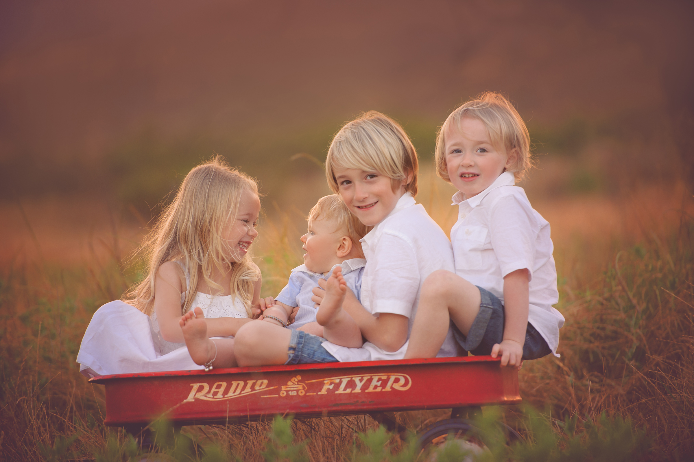 Siblings sit in a field in a red radio flyer wagon with baby brother in San Diego, CA