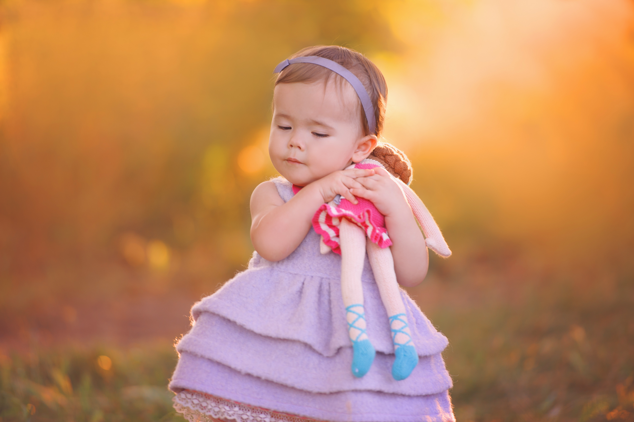 baby girl holds her doll for photography session during golden hour San Diego