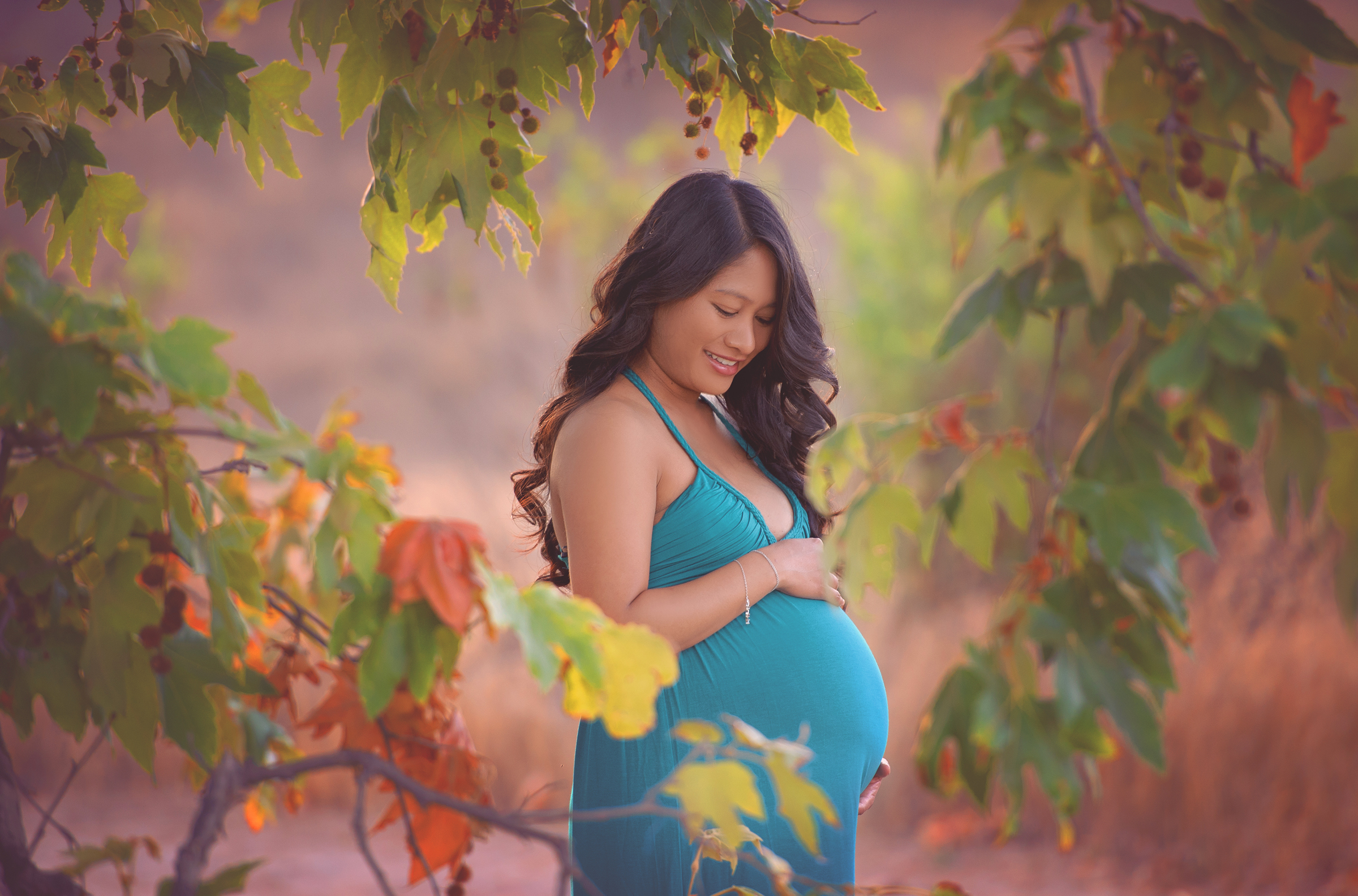 Maternity session through a heart shaped cutout of leaves in San Diego