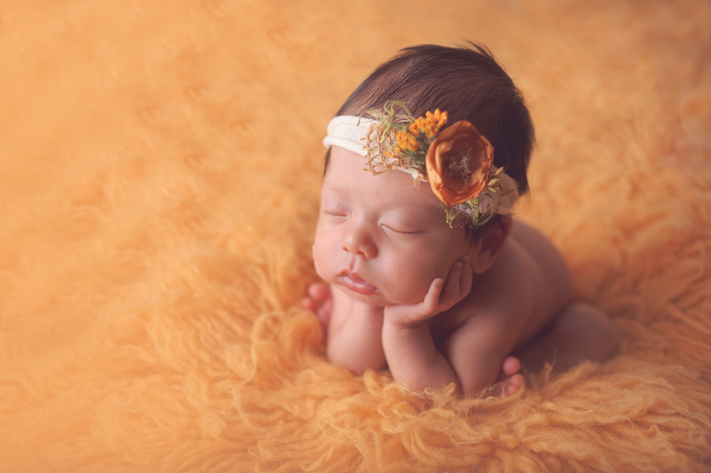 Newborn baby girl posed on yellow rug with cute headband in California newborn photography session