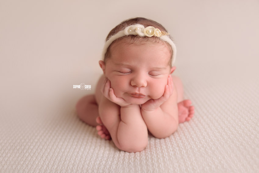 Newborn girl in froggy pose during her studio photo session on white blanket