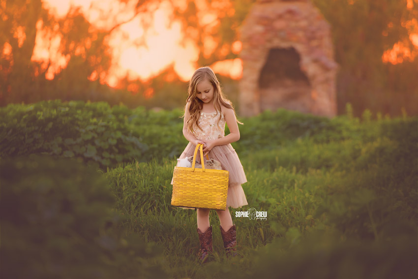 Girl holding a yellow basket with baby bunnies for a magical photoshoot in San Diego