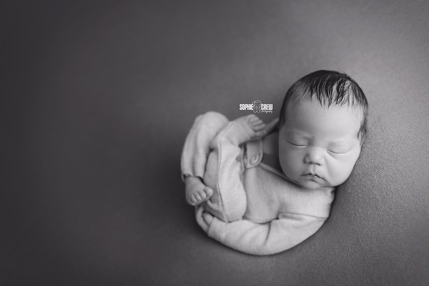 Black and white image of newborn curled on beanbag