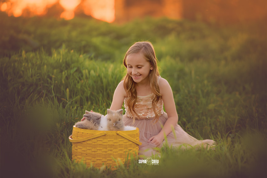 Child with basket of bunnies during outdoor nature photography session in San Diego