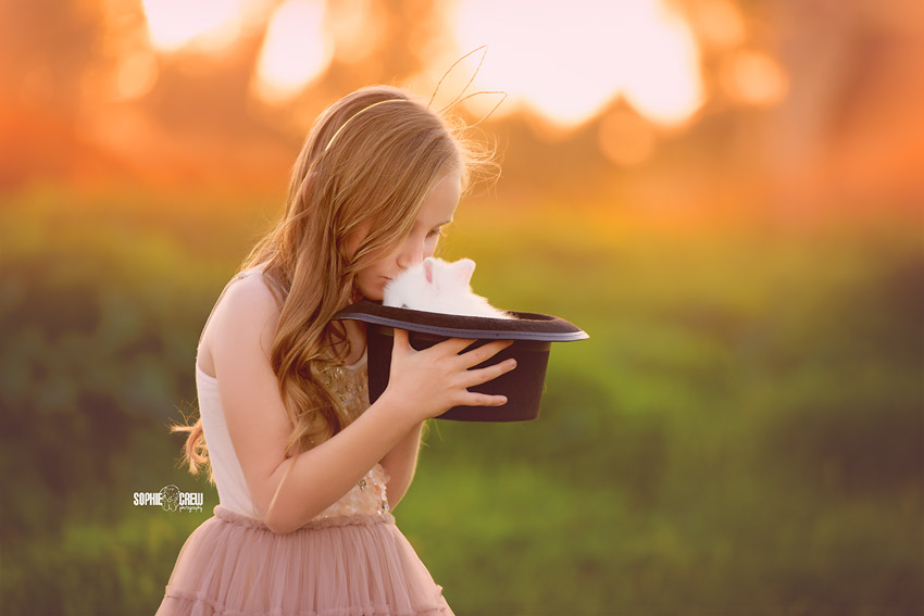 Girl kisses a baby bunny in a magician's hat for photo session