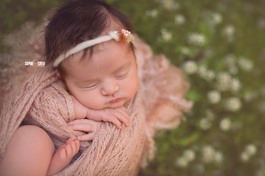 Close up of newborn wrapped in pale pink delicate wrap while posed for her outdoor newborn photo session