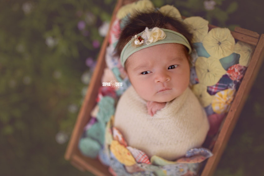 Newborn girl swaddled and awake for her outdoor newborn photography session