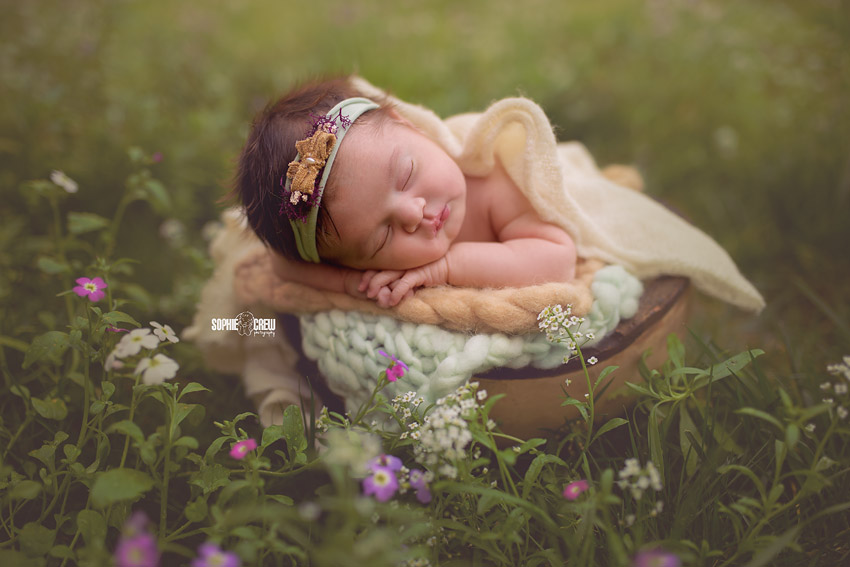 Newborn girl rests her head on her arm for newborn photos in san diego outdoor photo