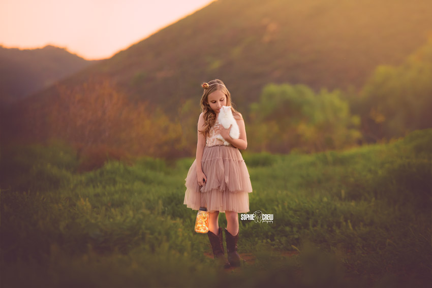 Child holding a live bunny and lantern at dusk