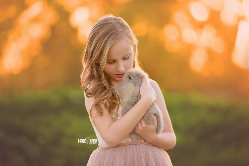 Little girl talks to her baby bunny for her San Diego Photography session