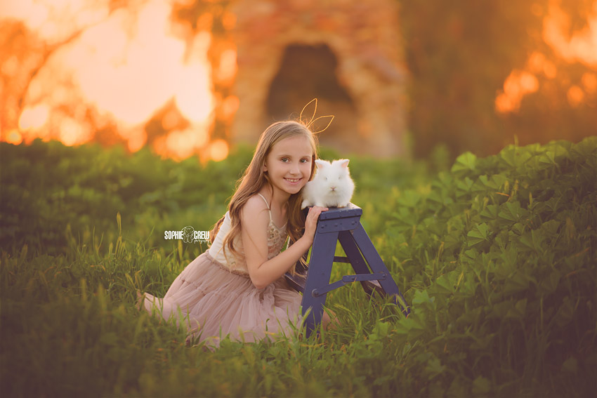 Girl posed next to bunny for her 9 year old photography session in San Diego, CA