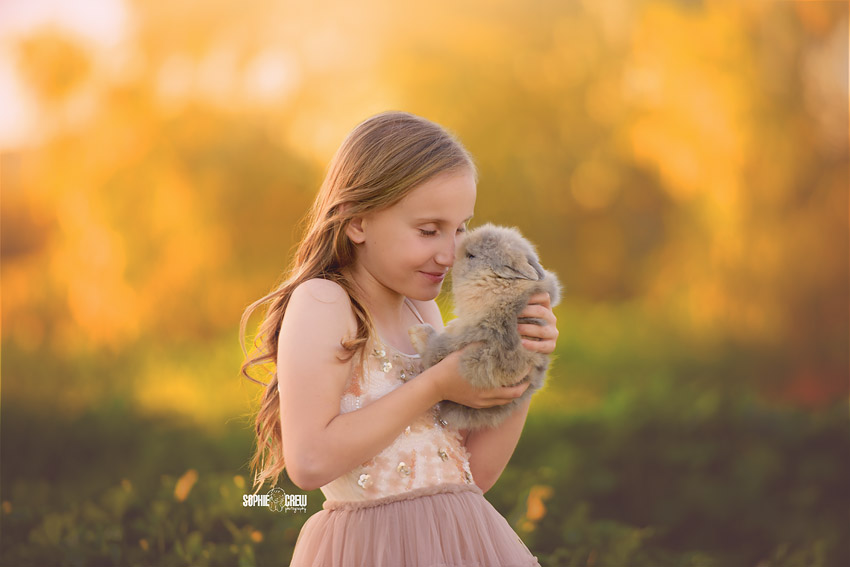 Girl gives eskimo kisses to a gray baby bunny for photography session with Sophie Crew Photography
