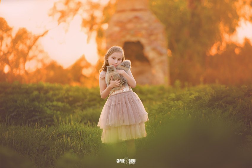 Little girl holds two baby bunny rabbits for her photography session