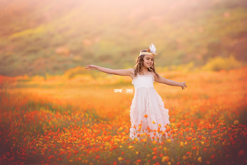 Girl dances in yellow and orange flowers in San Diego County
