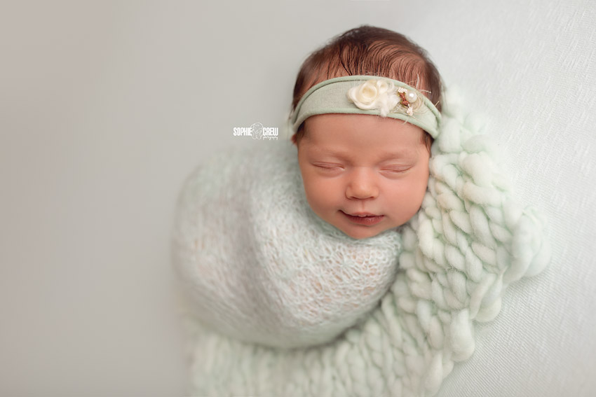 infant swaddled in wool teal wrap on beanbag