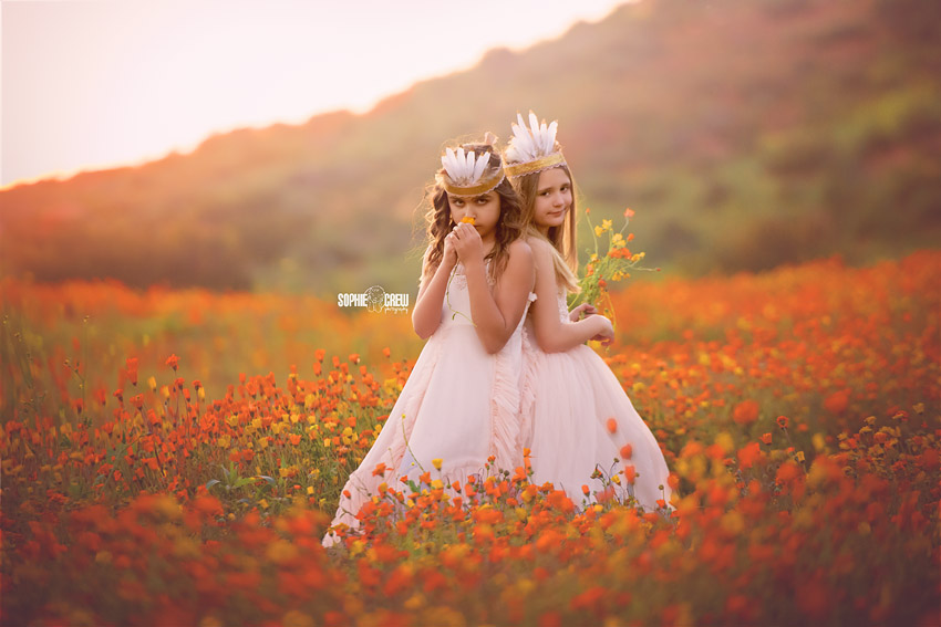 Girls holding flowers in wild flower field of orange flowers in San Diego location for family photogrpahy