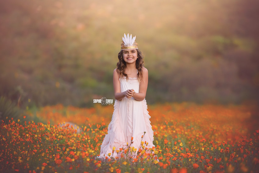 Emma stands in a field of orange flowers in San Diego for her photography session with her mom Sophie Crew