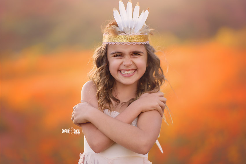 Girl wearing white and gold feather DIY crown in field of orange flowers