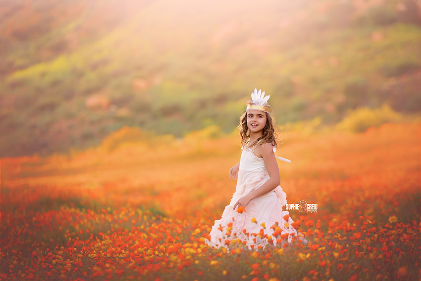 Young girl dances in orange wildflower field in San Diego wearing a feather crown and dollcake designer dress