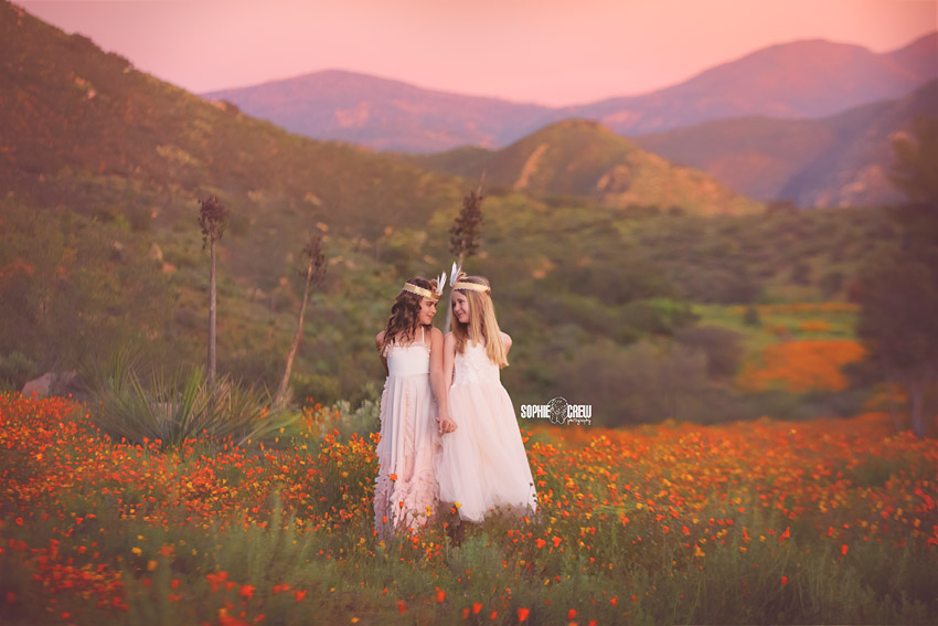Girls after sunset in orange flower field for mini child stylized session in San Diego