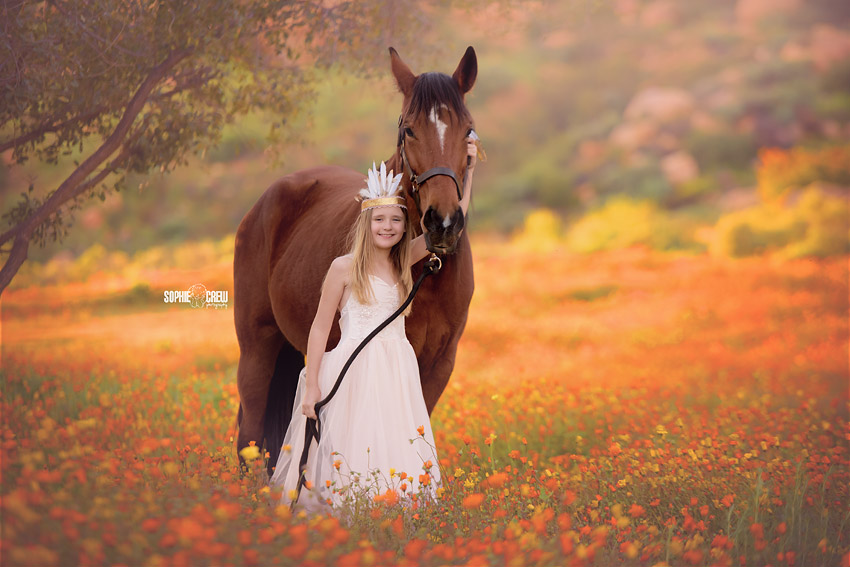Girl holds her horse in wildflowers in San Diego