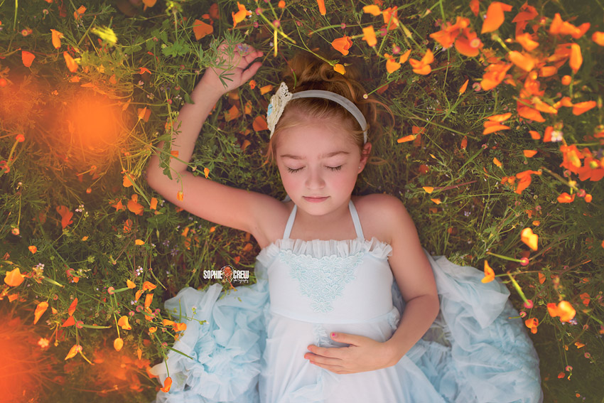 San Diego child pretends to sleep in field of orange flowers in San Diego, CA