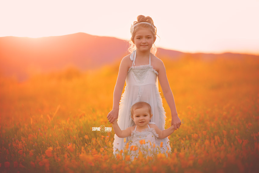 Baby and Big sister in Dollcake dresses pose in a field of orange California poppies during the wildflower superbloom