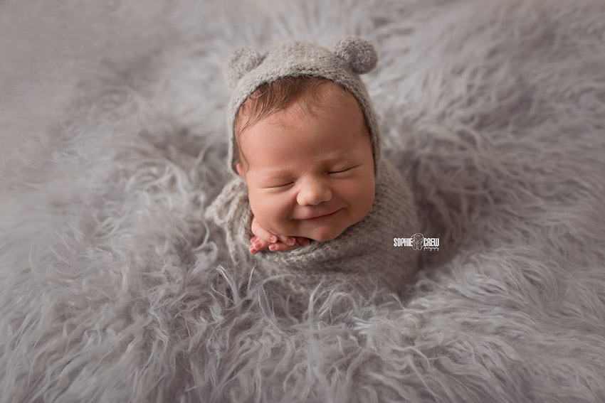 Newborn potato sack pose in gray bonnet and gray fur layer