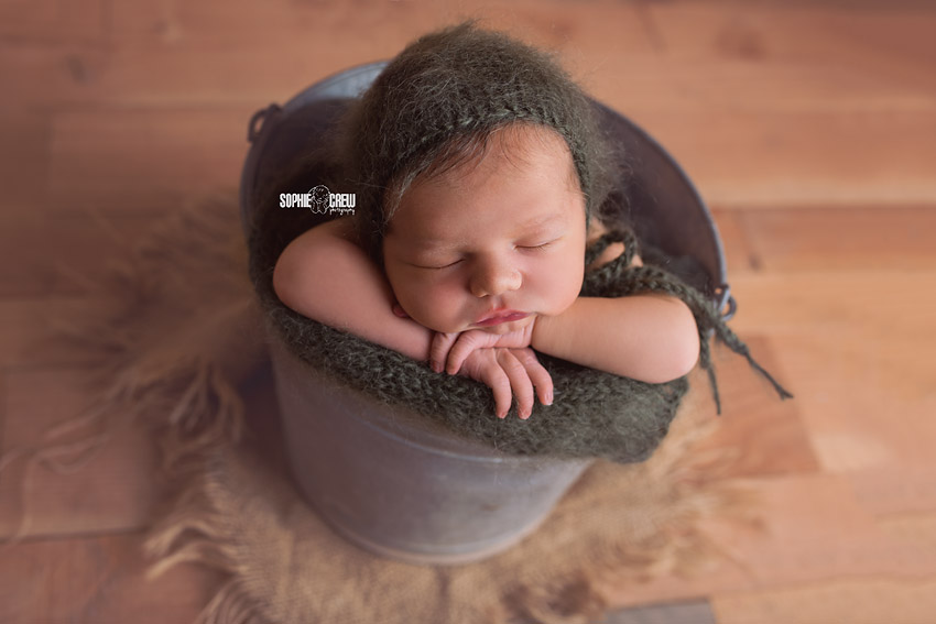 San Diego newborn photographer Sophie Crew shares an image of a baby boy posed in a metal bucket with green bonnet and blanket sleeping during his newborn photo shoot