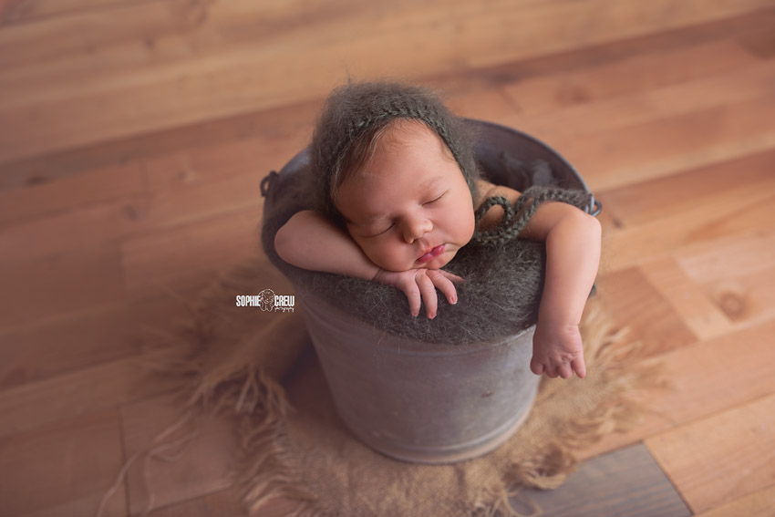 Newborn baby posed in a metal bucket with moss green bonnet and blanket in baby photography studio in San Diego