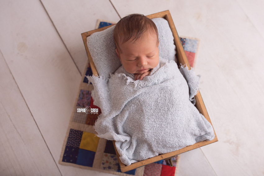 Newborn boy in blue blanket posed with a quilt pillowcase
