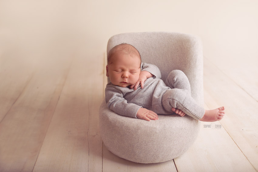 newborn baby boy posing in gray chair in San Diego