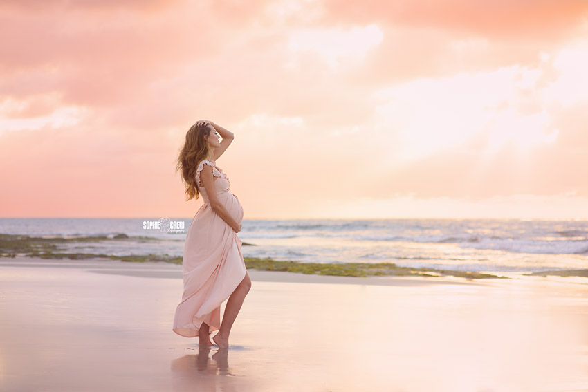 Maternity photography session on a San Diego beach with peach and pink cloudy skies and light pink maternity gown