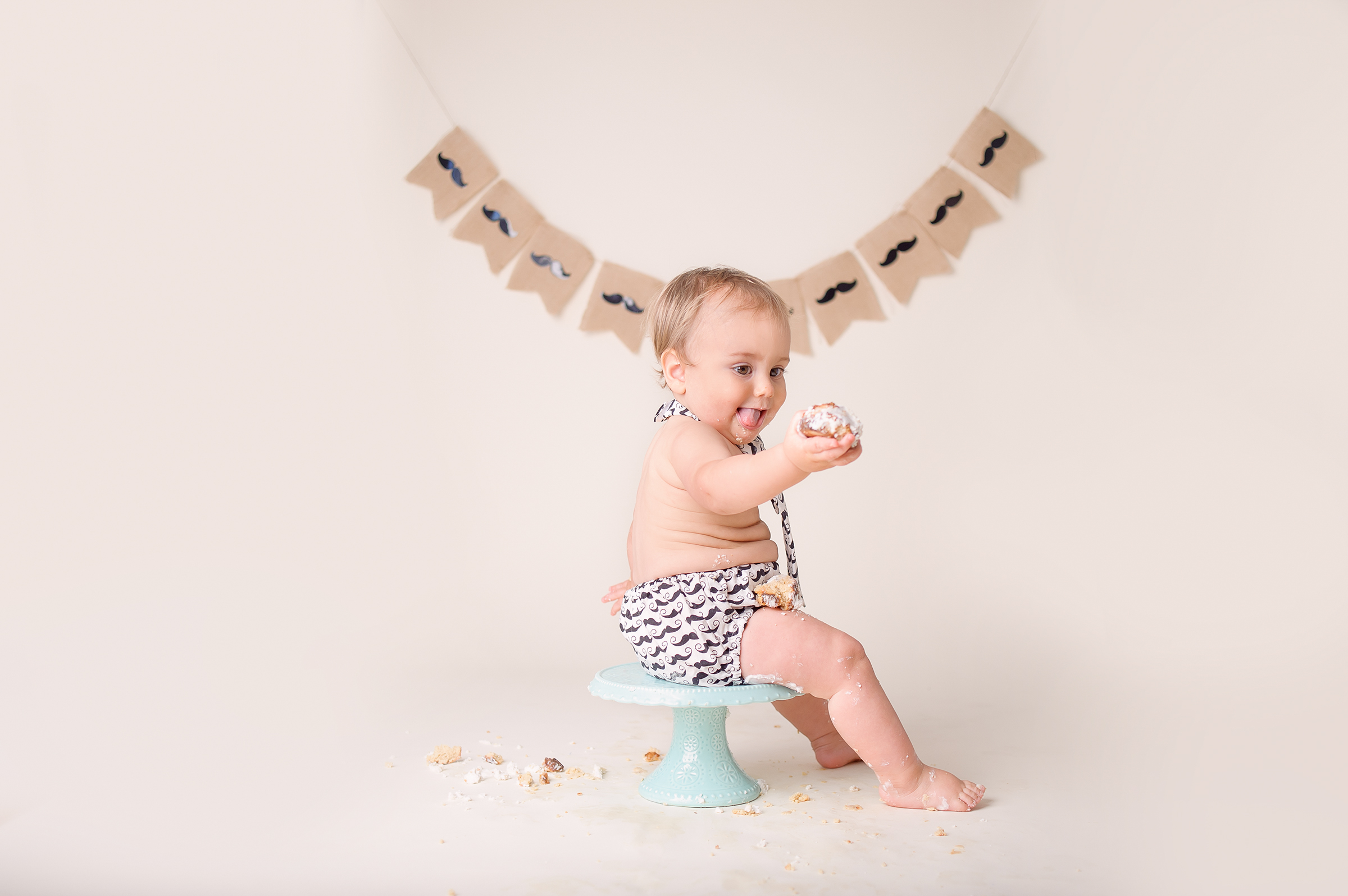 Funny expression from baby during cake smash photo session in San Diego baby photography studio