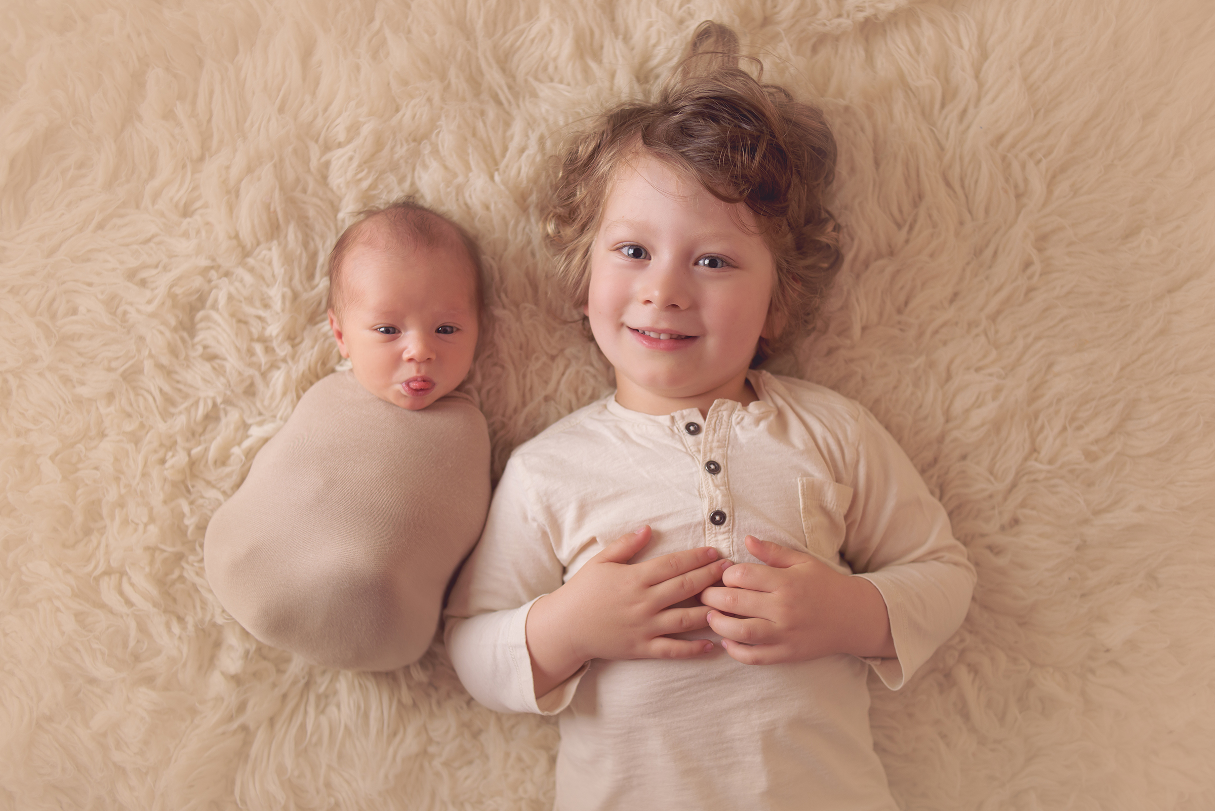 Big and little brother pose for newborn portraits during family baby photography session