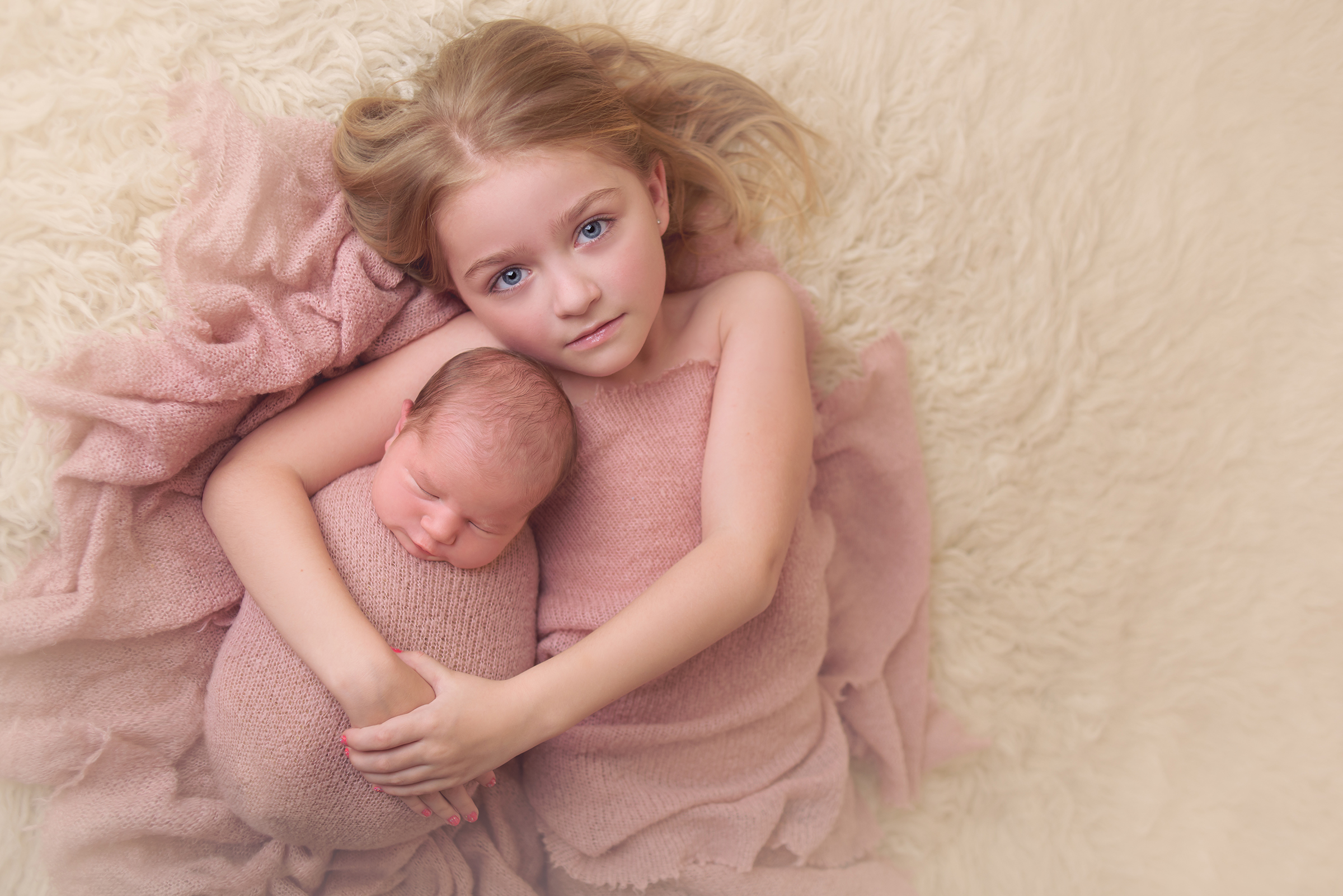 Beautiful image of big sister and newborn baby sister during infant photography session in Fallbrook