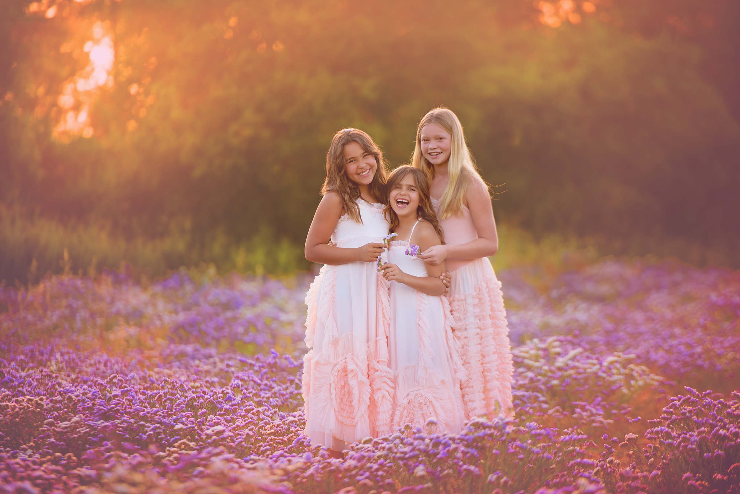 Tween and little girl pose in a sunny flower field of purple wildflowers in photography location in San Diego, CA