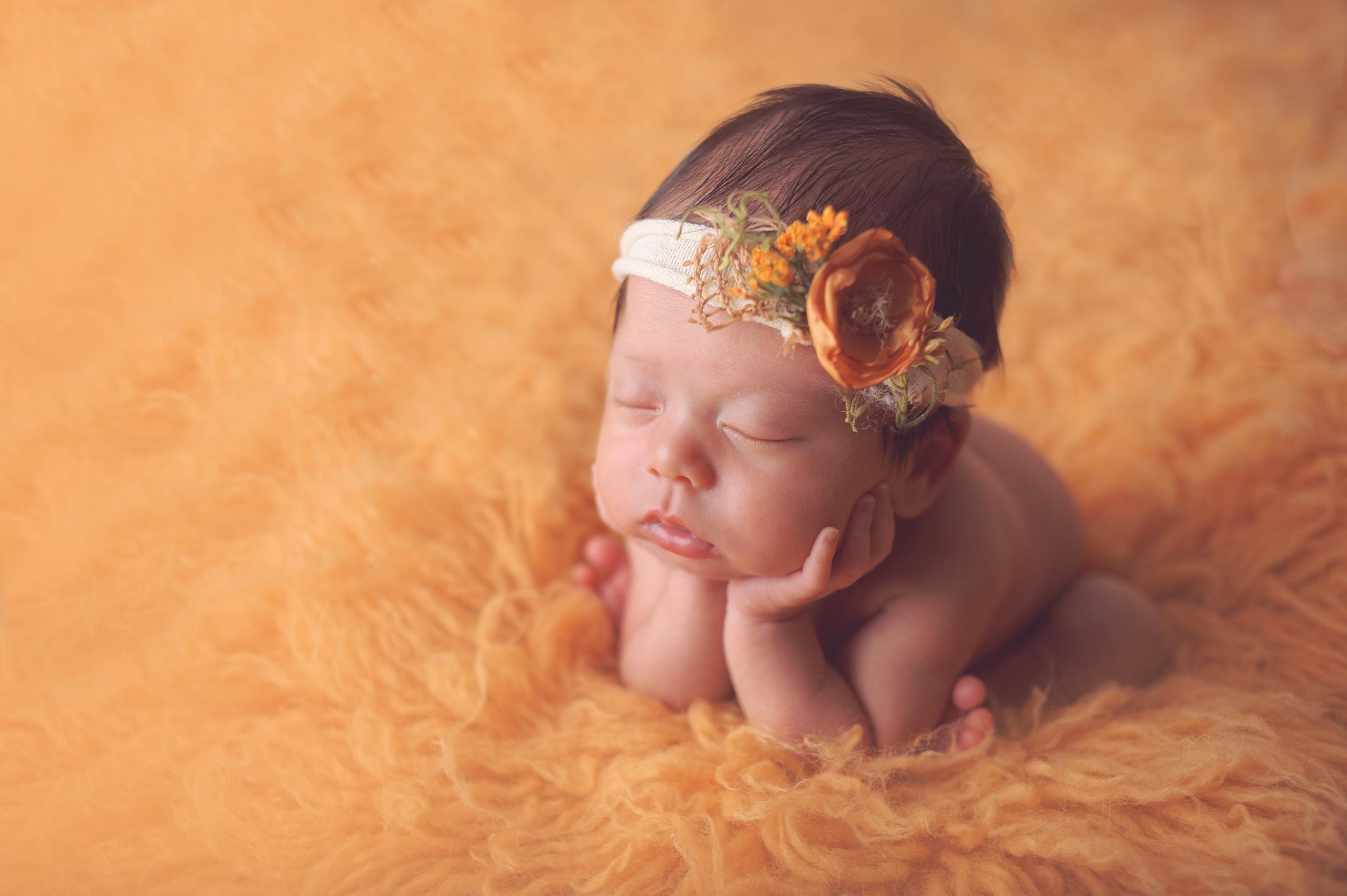 Newborn baby girl posed on yellow rug with cute headband in California newborn photography session