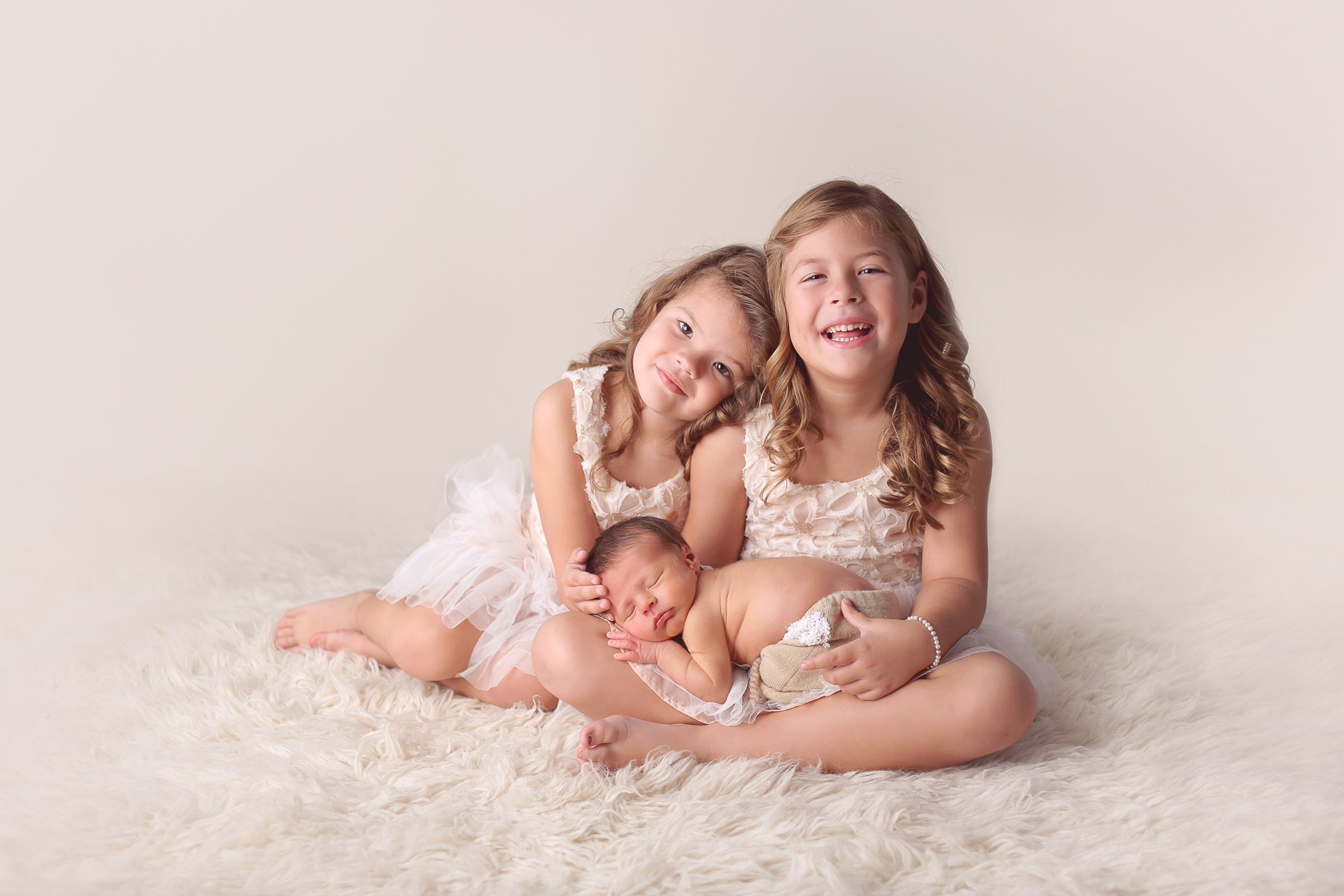 Siblings posed with infant newborn baby brother on white flokati rug in La Jolla photography studio