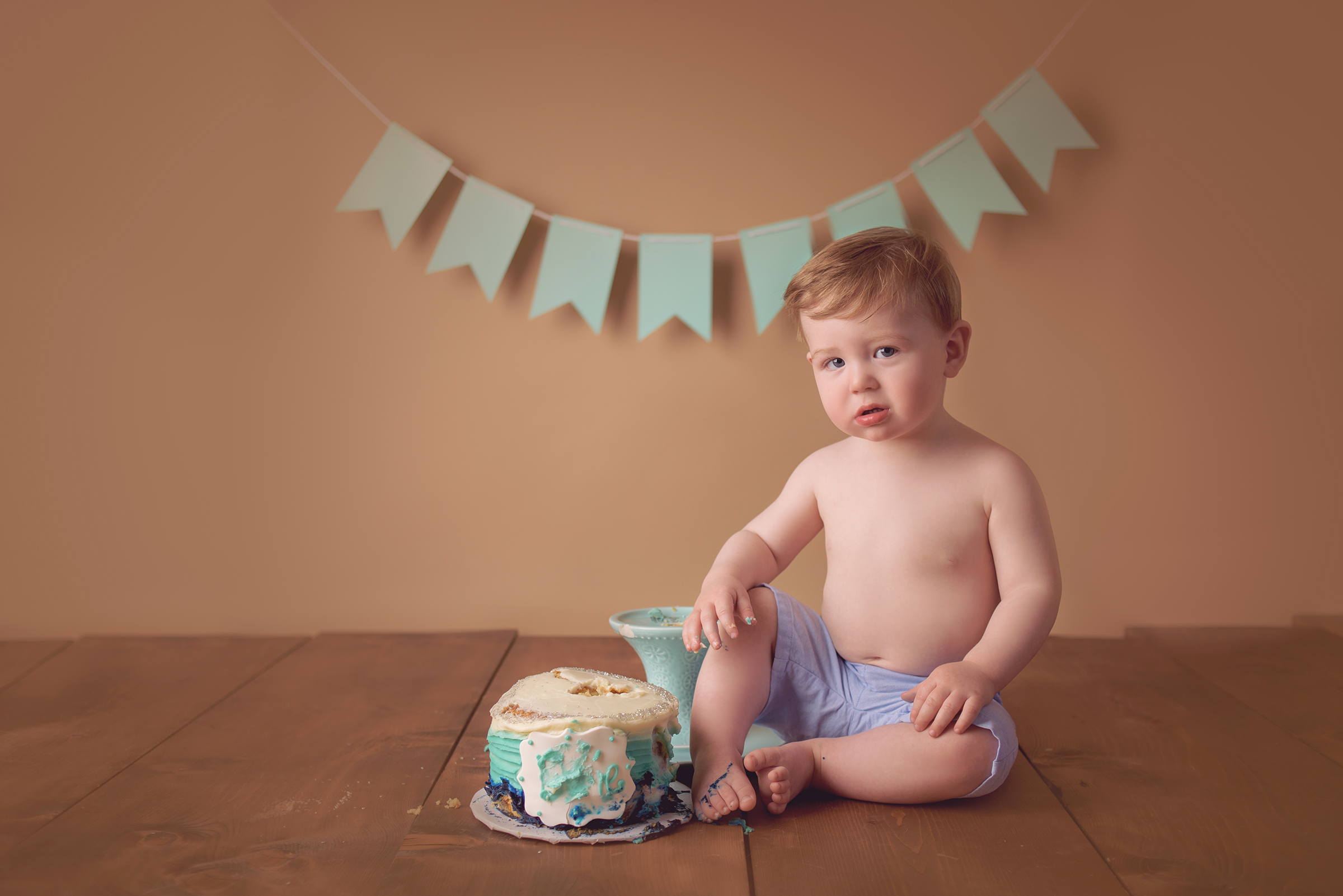cute picture of baby dropping birthday cake during smash the cake photography session in San Diego